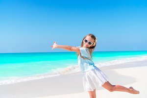 Amazing little girl at beach having a lot of fun on summer vacation. Adorable kid jumping on the seashore