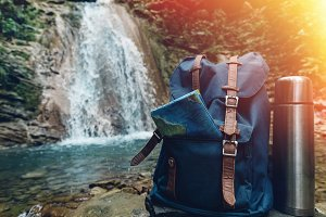 Hipster Blue Backpack, Map And Thermos Closeup. View From Front Tourist Traveler Bag On Waterfall Background