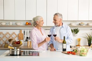 Mature happy loving couple standing at the kitchen drinking wine