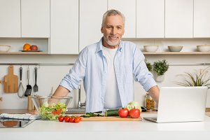 Mature attractive man standing at the kitchen cooking