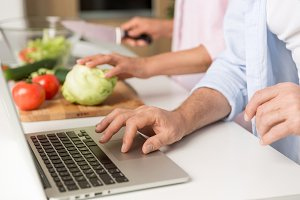Cropped photo of mature loving couple family using laptop cooking