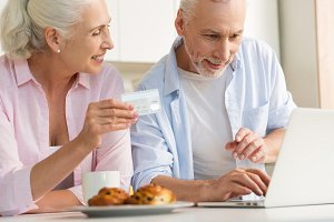 Happy mature loving couple family using laptop holding credit card