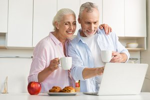 Happy mature loving couple family drinking tea using laptop