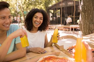 Happy young multiethnic friends students outdoors drinking juice eating pizza