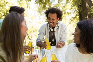 Cheerful young multiethnic friends students outdoors drinking juice