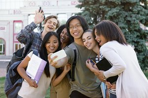Multiethnic group of young happy students make selfie outdoors