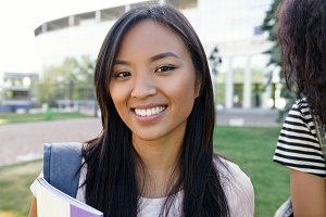 Happy student asian woman standing outdoors