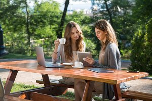 Smiling women sitting outdoors in park drinking coffee using laptop
