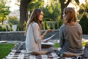 Smiling young two women sitting outdoors in park writing notes