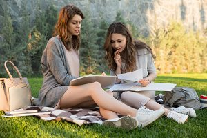 Smiling young two women sitting outdoors in park writing notes.