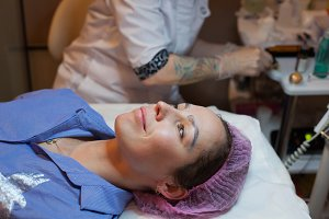 Girl is getting ready for permanent make-up. Permanent tattooing of eyebrows. Cosmetologist applying permanent make up on eyebrows- eyebrow tattoo