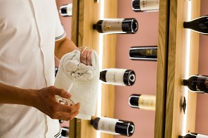 A young bartender is wiping towel wine glasses at work in the restaurant on the background of bottles of wine