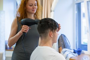 Male client getting haircut. Girl hairdresser dries my hair a young, attractive guy in a beauty salon