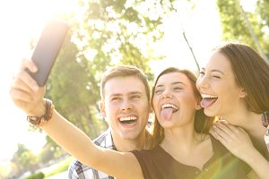 Three funny teens taking selfies