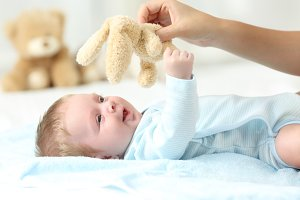 Mother hand holding a teddy and baby