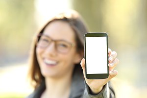 Happy woman showing a smart phone