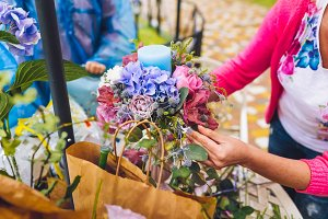 Florist making a flower composition. Wedding details. Woman collecting a composition of different, colorful flowers and a blue candle.