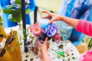 Florist at work, making a flower composition. Wedding details. Woman collecting a composition of different, colorful flowers and a blue candle.