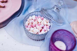 Colorful mini marshmallows in glassware on a white table with blue lace. Different mini white and pink puffy marshmallows. Marshmallow concept.