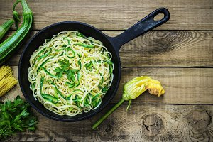 Pasta with zucchini on dark wooden background in a cast-iron frying pan . Spaghetti from organic wholegrain flour