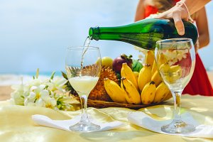 Man is pouring champagne into a glass on a background of a plate with fruit. Celebration on the beach