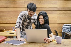 Multiethnic couple using laptop in a work space