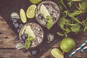 Blueberry mojito on rustic wood background
