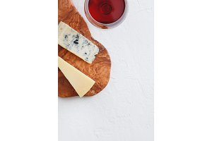The glass of red wine, blue cheese and parmesan on the beautiful wooden plank of olive wood on the textured white background. Copy space, top view.