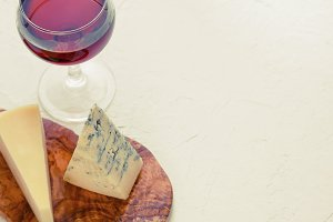 The glass of red wine, blue cheese and parmesan on the beautiful wooden plank of olive wood on the textured white background. Toned image, copy space.
