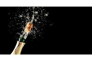 Champagne cork popping and splashing on black background