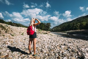 Beautiful young tourist girl with a bright backpack and in shorts stands on the bank of a mountain river and look at the mountains in summer