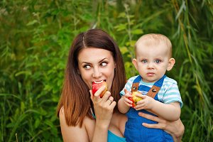 Mother and daughter eating apples.