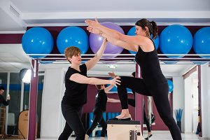 Young woman exercising on combo wunda pilates chair with personal instructor