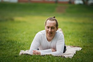A young yoga instructor relaxes in the park before practicing