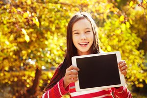 girl in autumn with tablet computer