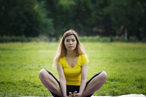 Young yoga girl in the park during class