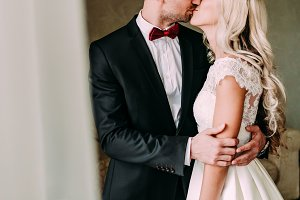 Happy newlyweds are kissing indoor. A blode bride and groom stand near the window. Wedding.