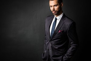 Handsome young businessman standing confident on black
