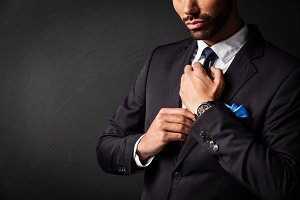 Attractive businessman fixing his tie.