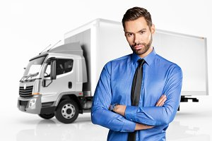 Businessman standing in front of a truck.