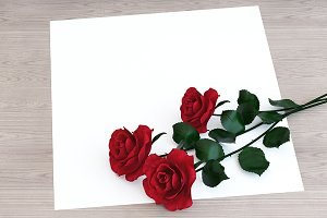 Red roses with paper on the table