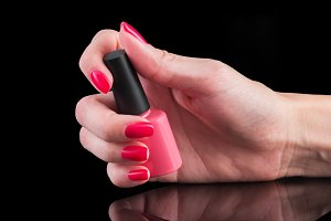 hand with pink manicure and vial