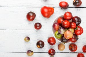 Different tomatoes in the bowl on the white wooden background