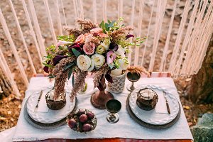 The composition of different flowers standing on served table in the area of wedding party. Floral arrangement.