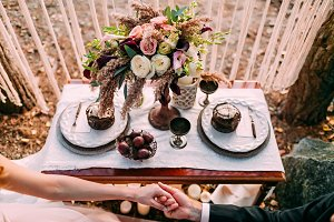 Wedding in the vintage style on outdoor. Couple holding hands. Flower composition