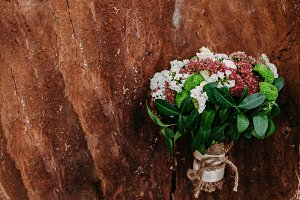 Rustic wedding bouquet with different flowers and greens on wooden background