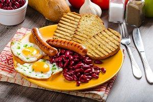 English breakfast - garlic toast, fried egg, beans and English breakfast, toast, egg, beans, sausages