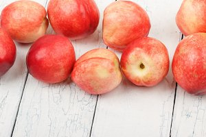 Ripe red peaches on the white wooden table