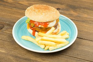 Tasty homemade burger served with fries on plate on a table.