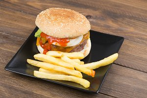 Tasty homemade burger served with fries on plate on a table. Food.